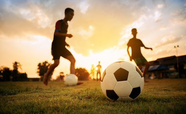 silhouete-action-sport-outdoors-group-kids-having-fun-playing-soccer-football